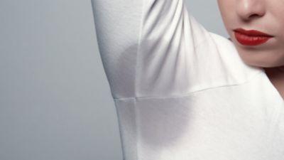 O pată mare de transpirație la subraț pe o cămașă albă.