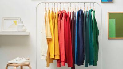 Bunte Kleidung hängt auf einer Kleiderstange.