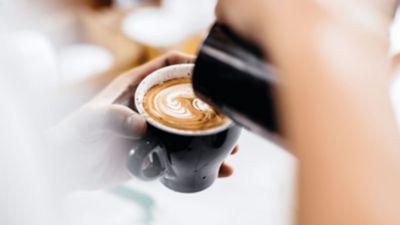 Bir cappuccino veya kahve üzerinde süt köpüğü ile bir desen oluşturuluyor.
