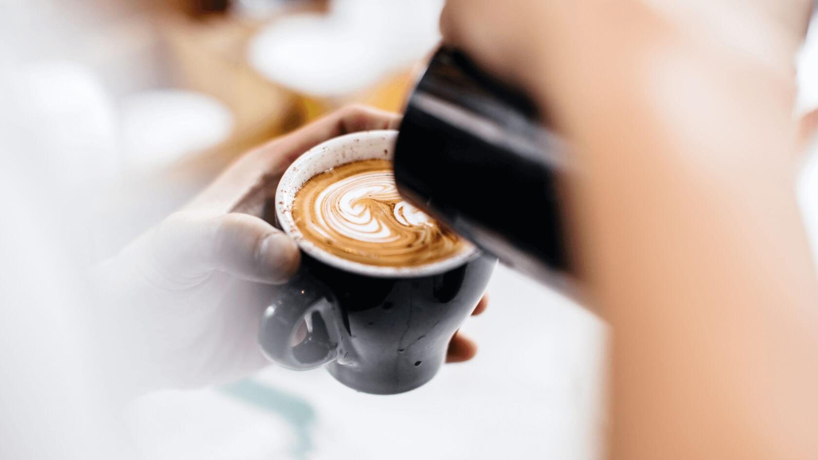 Auf einem Cappuccino beziehungsweise Kaffee wird mit Milchschaum ein Muster kreiert.