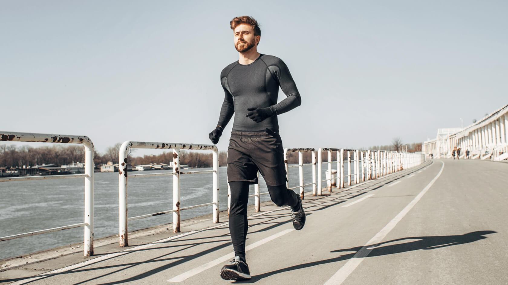 Ein Mann in Funktionskleidung beim Joggen am Ufer.