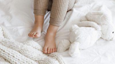 Kinderfüße auf weißer Bettdecke, daneben  ein strahlend weißer Plüschhase.