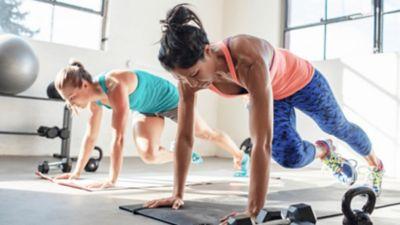 Eine Frau in Sportkleidung trainiert auf dem Boden, links von ihr eine andere Person, die ebenfalls trainiert.