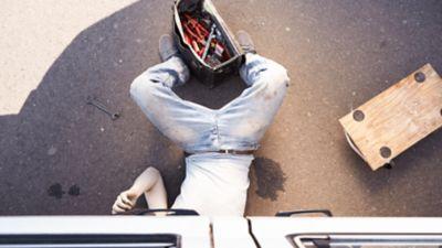 Ein Mann werkelt unter einem Auto, neben ihm ein Fleck aus Schmieröl und ein Werkzeugkasten in den Füßen.
