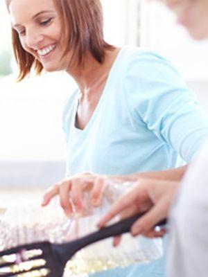 O femei care zâmbește turnând ulei dintr-o sticlă de plastic, o altă femeie, în cadru neclar în față, ține o spatulă în mână.
