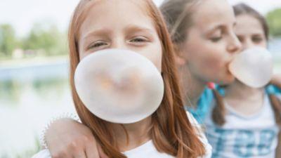 Ein rothaariges Mädchen macht eine große Kaugummiblase.