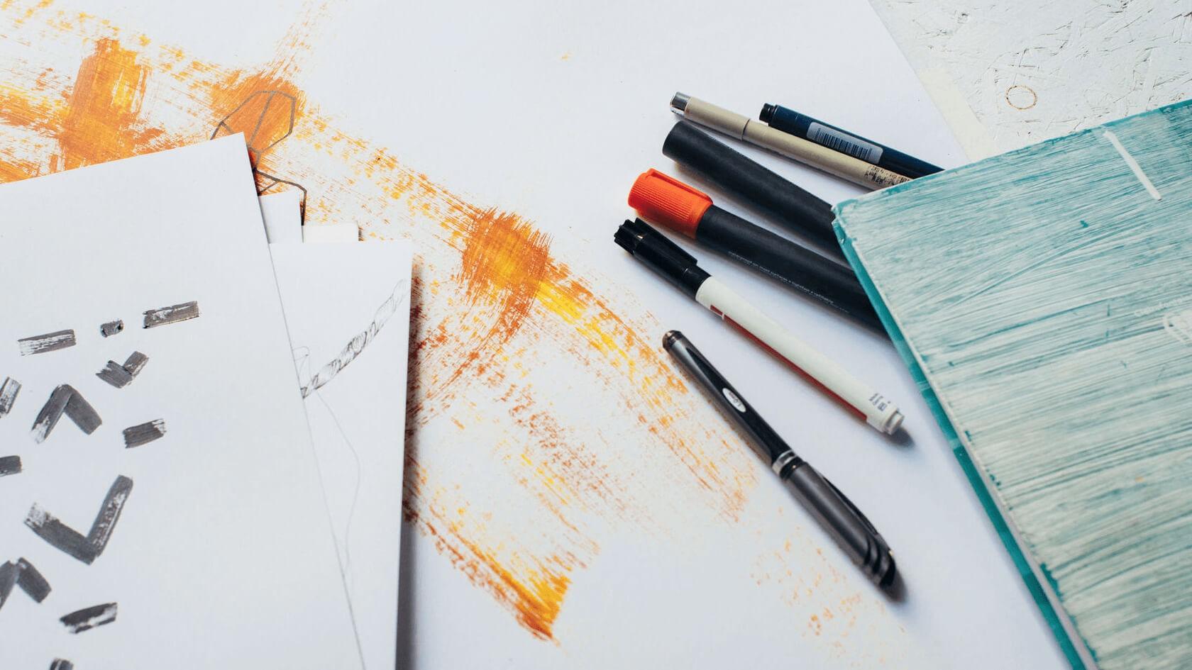 Verschiede Stifte liegen verteilt auf weißem Hintergrund, in der Mitte gemalte Streifen in Gelb, Orange und Braun.