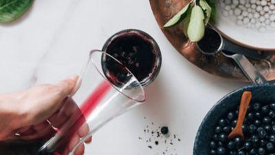 Yaban mersini suyu, bir cam sürahiden başka bir cam kaba dökülüyor, yanında masanın üzerinde yaban mersini dolu bir kase duruyor.