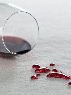 Un pahar de vin roșu răsturnat, pe covorul roșu câteva pete de vin.