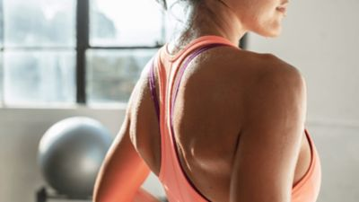 Rückenansicht einer Frau im Trainigsshirt und Schweißperlen auf der Haut.