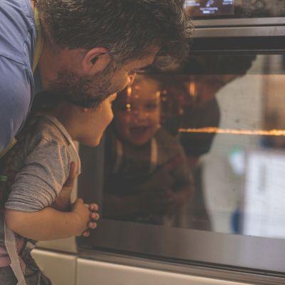 Mann und Kind beobachten, wie eine Pizza im Ofen aufgeht