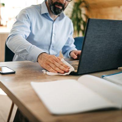 Mann reinigt den Lüfter seines Laptops