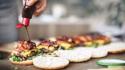 BBQ-Sauce wird auf üppig belegte Burger getröpfelt.
