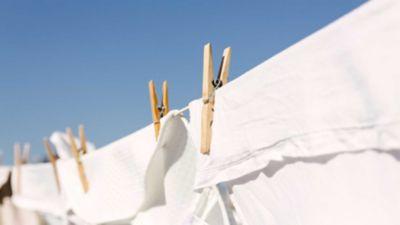 Zwei Wäscheklammern aus Holz fixieren weiße Wäsche an der Leine.