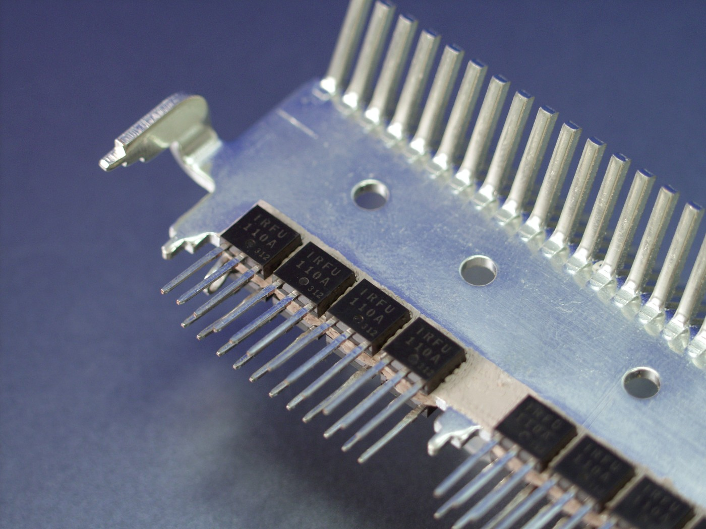 Photo of Bergquist Bond Ply thermally conductive adhesive tape used as interface material between a row of power transistors on a metal heatsink