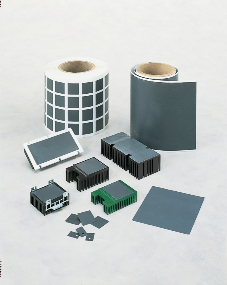 Photo of grey bergquist phase change thermal interface material on spools and applied to components of various shapes and sizes represents an effective alternative to thermal greases