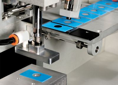 Close up photo of blue rectangular sil pads with circular hole in center being manufactured and placed on tape by automation equipment