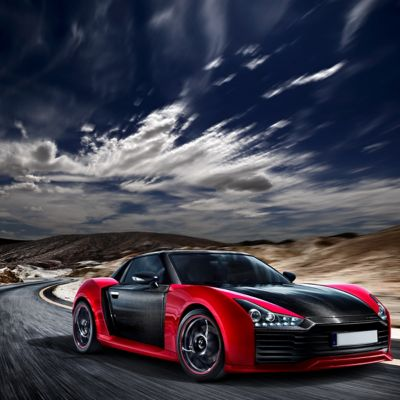 Red and Black Roding Roadster driving fast through mountains
