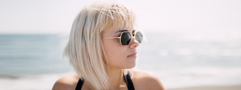 Blonde Frau mit Bob-Haarschnitt, fransigem Pony und Retro-Sonnenbrille