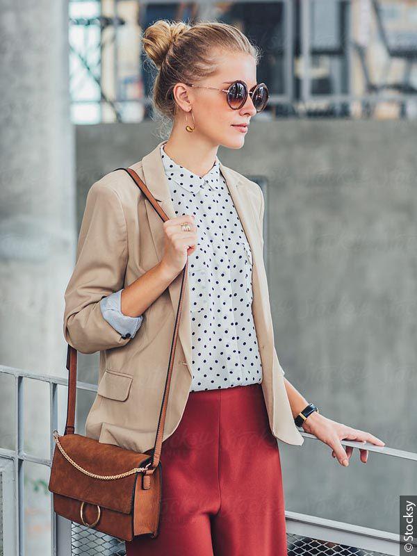 Blonde Frau mit Chignon und Sonnenbrille im Business-Outfit
