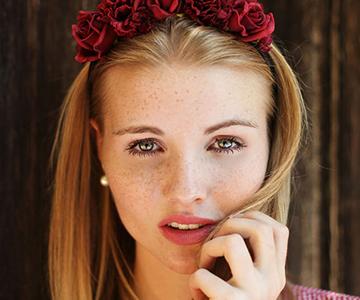 Blonde Frau mit glatten Haaren, rotem Haarschmuck und karierter Bluse