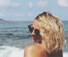 Blonde Frau mit welliger Strandfrisur und Sonnenbrille