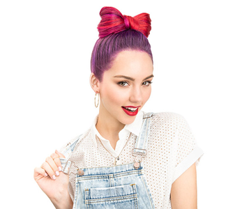 Woman with pink and purple hair in a bow bun and wearing dungarees