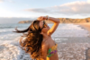 A brunette woman wears bikini and sunglasses on the beach