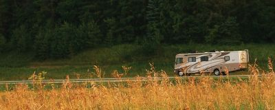 Recreational Vehicle Driving On The Road With Trees in Background