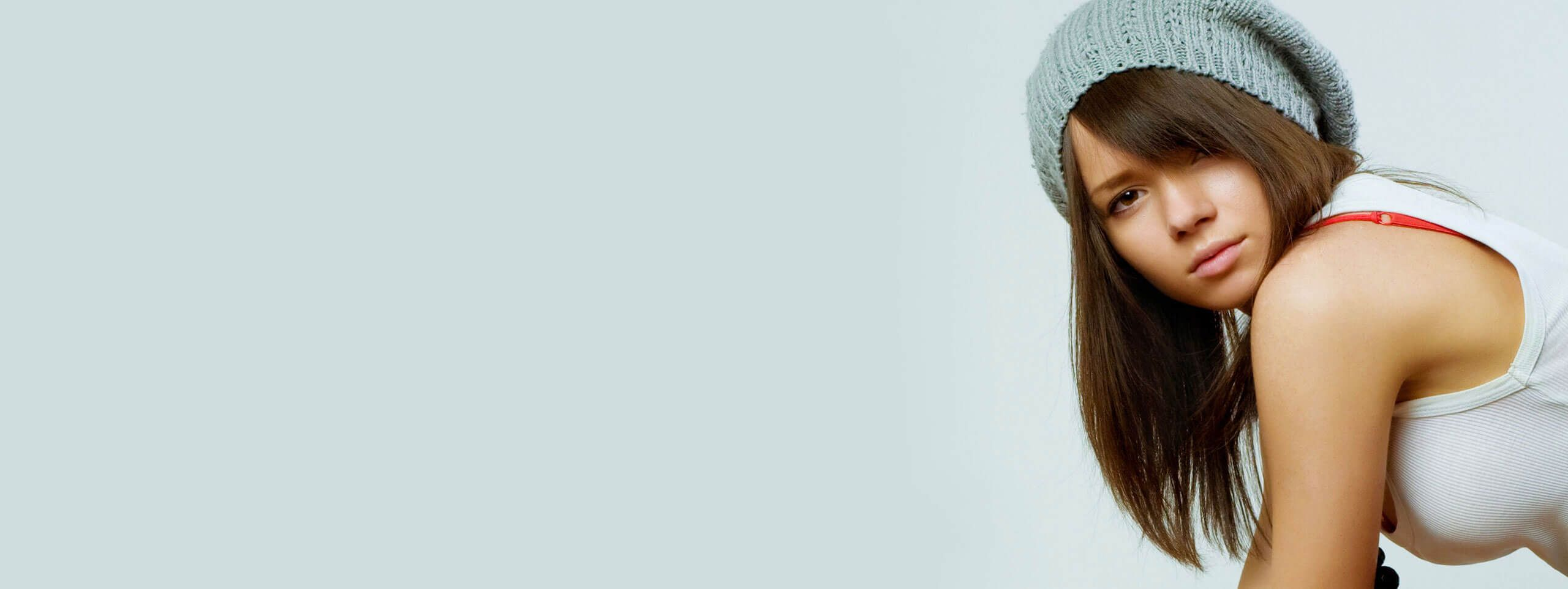Brunette model wears beanie hat with straight hairstyle and side fringe