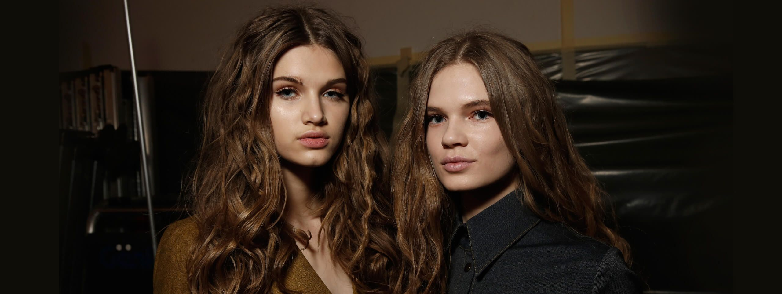 Brunette models wear loose curly hairstyle with flat roots