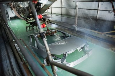 Car bodies dipped into a surface treatment inside an automotive manufacuring factory