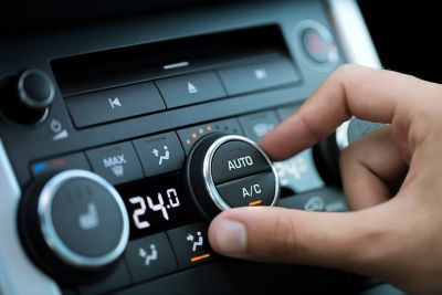 A hand turns the auto/AC dial of a car's HVAC control panel