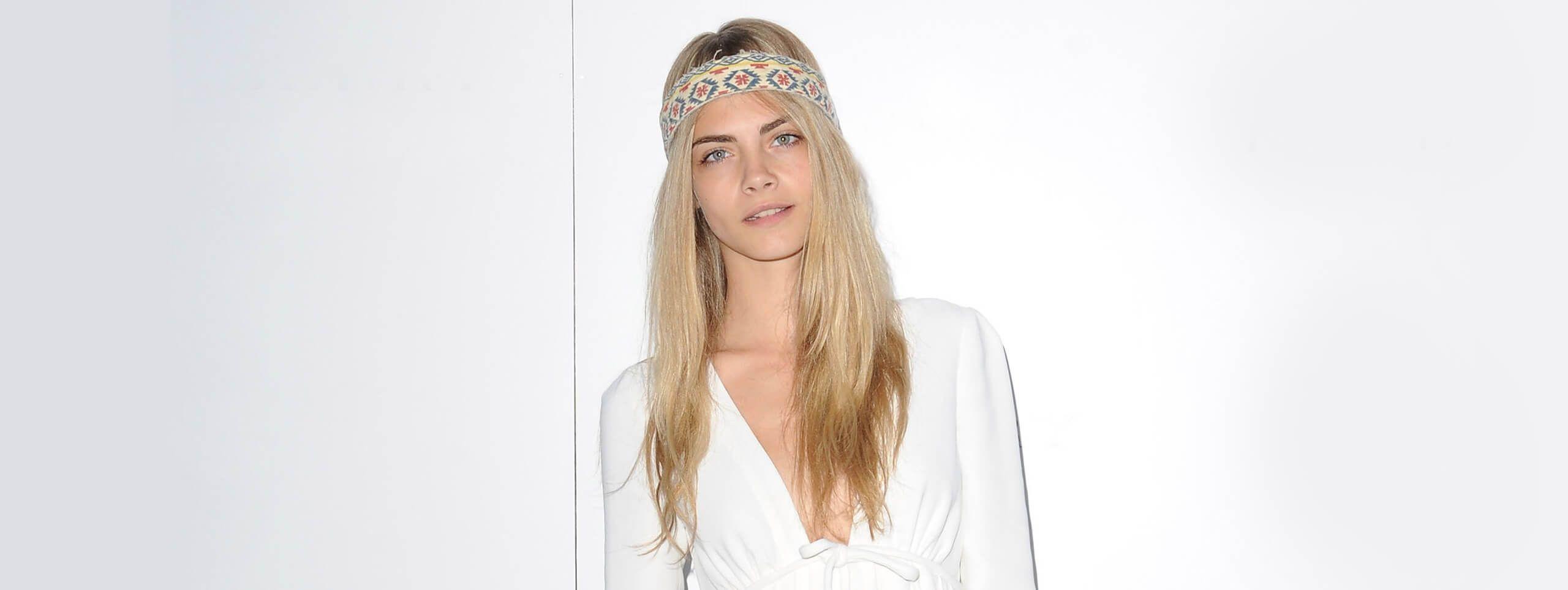Cara Delevingne z rozpuszczonymi długimi blond włosami i opaską