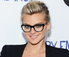 Celebrity with thick-framed glasses and tied back hairstyle
