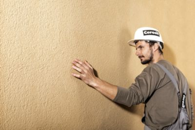 Строитель, проверяющий состояние стен.