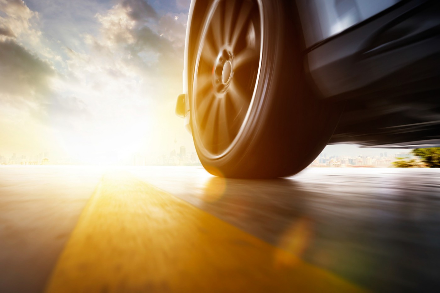 Close up of vehicle tire driving fast at sunset