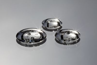 Closeup of three shiny droplets of automotive cleaner