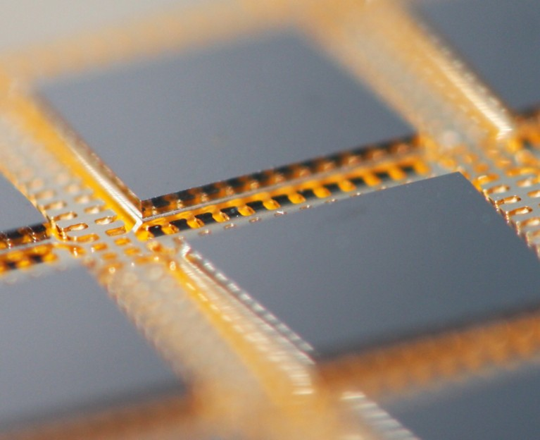 Closeup photo of copper leadframe packaging with integrated circuit attached with conductive die attach film
