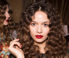 Women with corkscrew curls getting ready for a fashion show