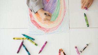 Kind malt Regenbogen mit Wachsmalstiften