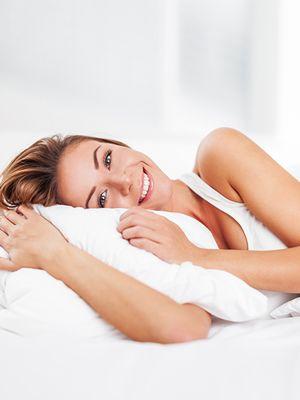 nasmijana žena leži i rukama grli bijeli jastuk