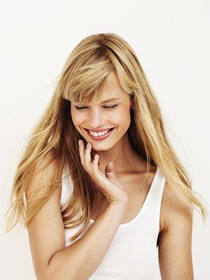 Nasmijana žena nježno dodiruje lice