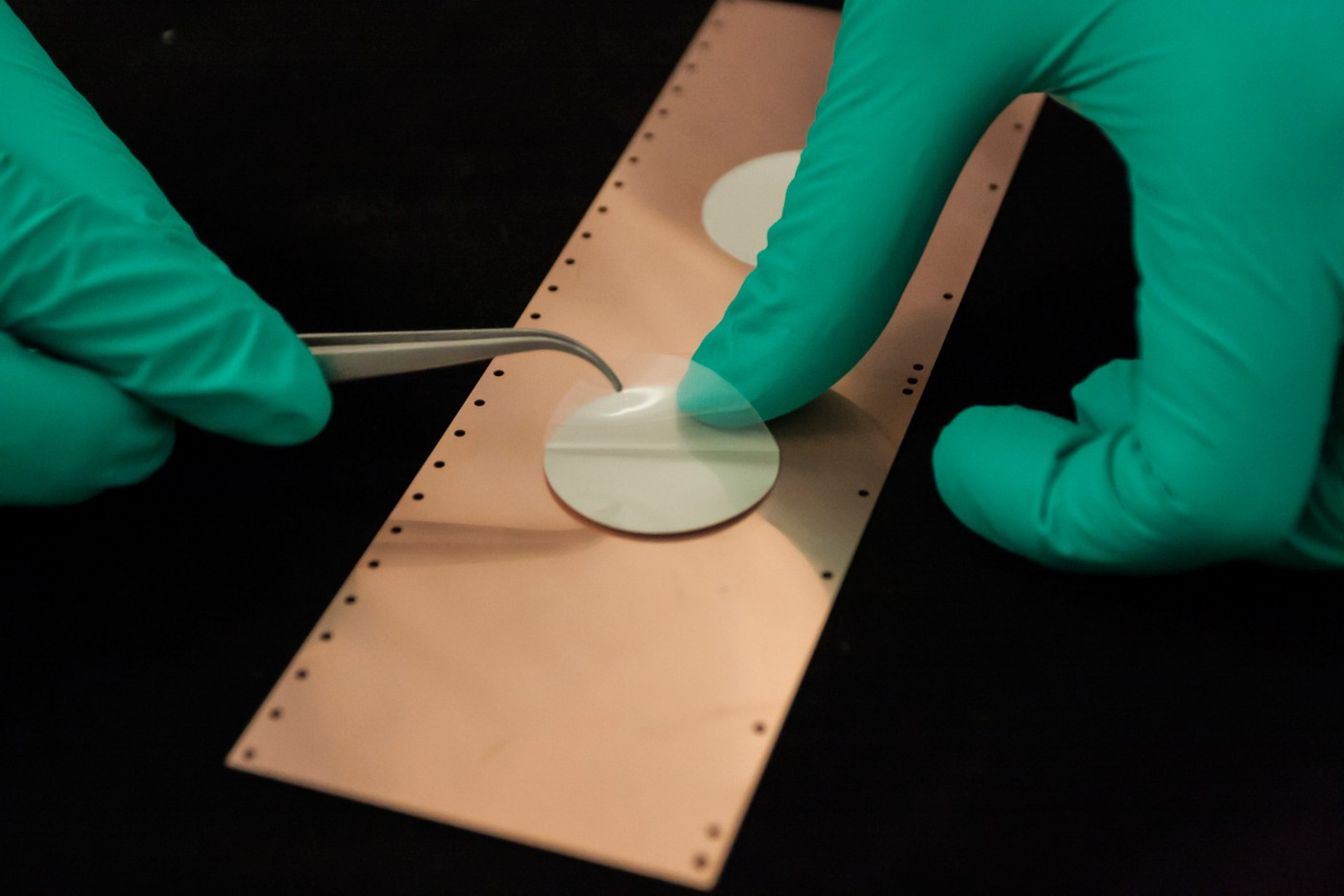 Photo of hands with green gloves using tweezers to peel film covering from loctite ablestik cf 3366 preformed thermallly and electrically conductive adhesive material attached to a copper plate with black background