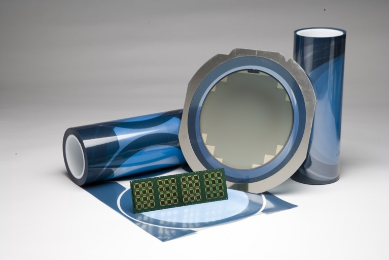 Photo of blue die attach film adhesive in rolls and on components