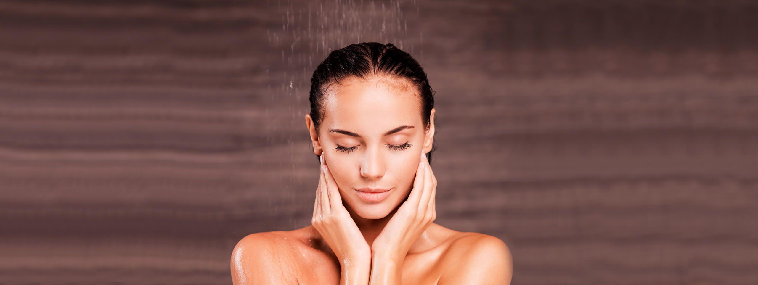 Donna che si lava i capelli sotto la doccia
