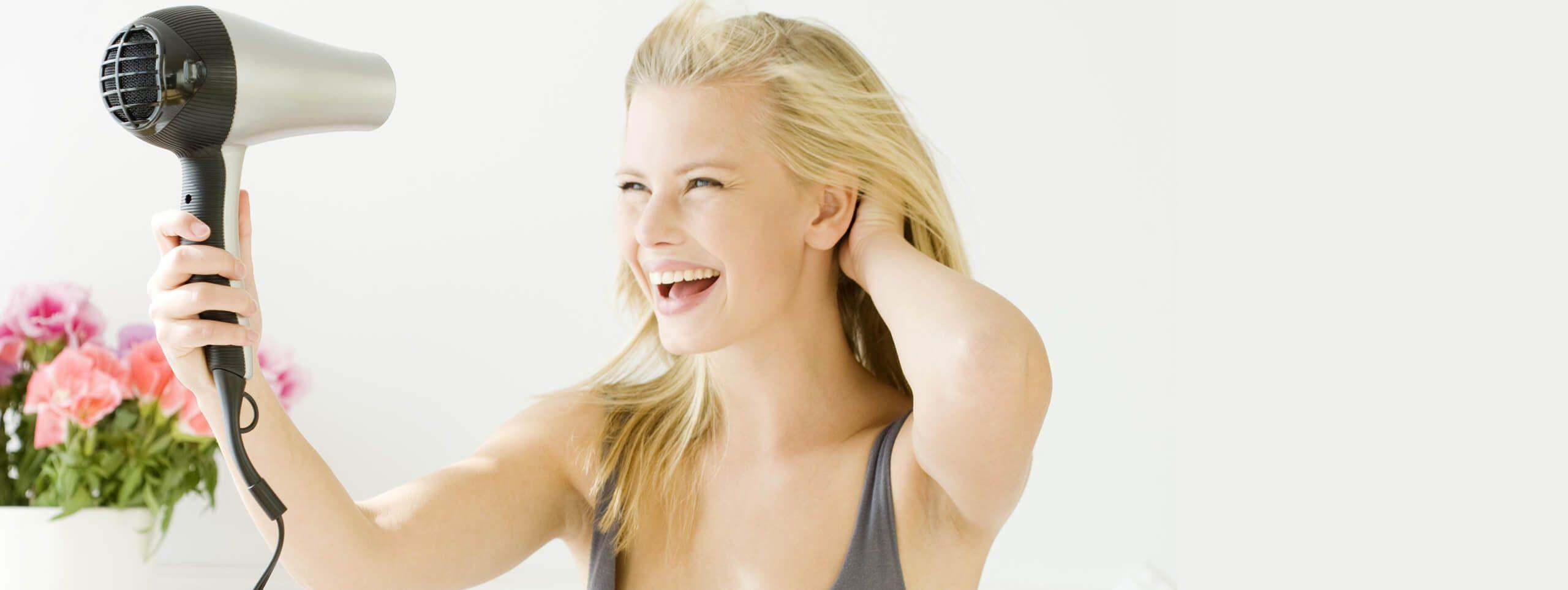 Protezione dal calore dei capelli: donna con i capelli biondi che mantiene l'asciugaapelli ad una distanza di sicurezza