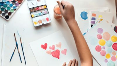 Kinderhände malen mit Wasserfarben rote Herzen auf ein weißes Blatt Papier.