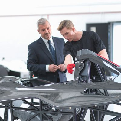 Two men examine an automotive composite car body
