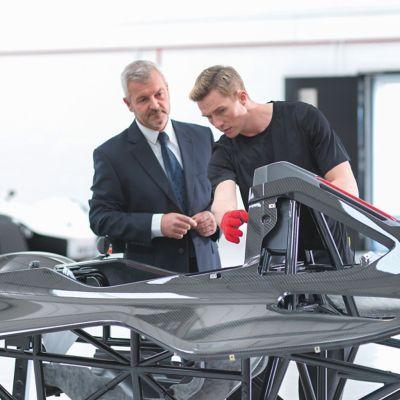 Two men examine an automotive composite car body